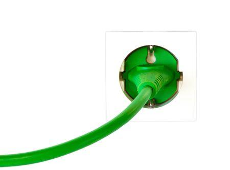 Groene stekker in eenvoudige stopcontact tegen een witte achtergrond