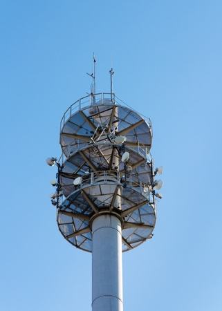antennae: Communication mast for various antennae and dishes against blue sky Stock Photo
