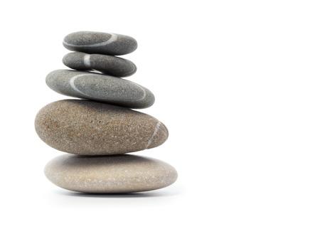 Stack van evenwichtige stenen tegen een witte achtergrond Stockfoto