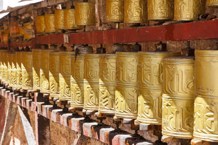lamaism: Gold colored Buddhist prayer wheels in the city center of Lhasa, Tibet