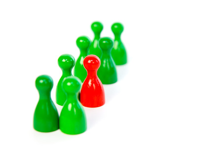 lineup: Red pawn in a line-up of green pawns against white background Stock Photo