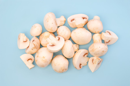 champignon: Bunch of mushrooms, a few cut, from a top view against light blue  Stock Photo