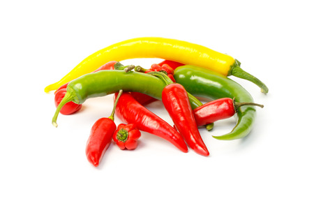 Group of colored hot peppers against white background