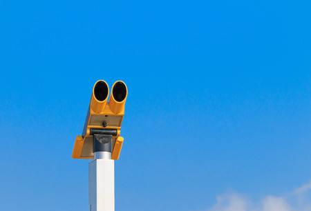 Public coin operated binoculars against blue sky photo