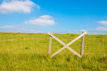 dike: Fencing at grassy dike and blue sky with clouds