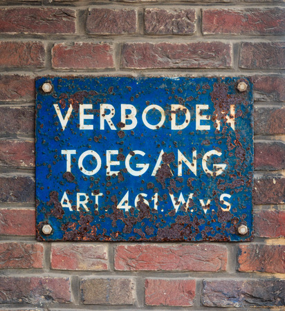 Rusty old plate on brick wall with Dutch text No Trespassing photo