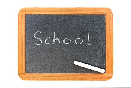 School written on vintage chalkboard and a chalk on the board, isolated on white photo