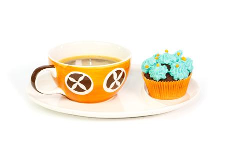 escarapelas: Taza de caf� y una magdalena con rosetas azules de crema frosting contra el fondo blanco