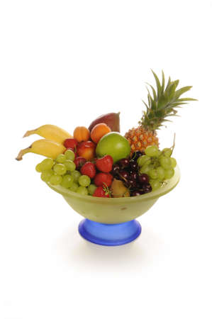 juicy and fresh fruit in a two-colored glass bowl photographed with white background in studio photo