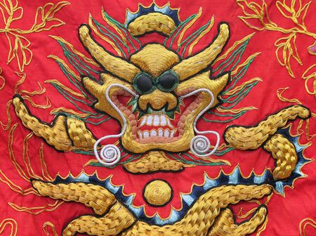 red and gold: Tapestry of a Golden Dragon on a Red Silk Background Stock Photo