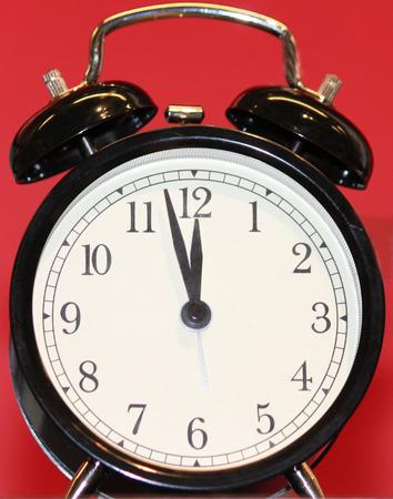 赤い背景とレトロな黒目覚まし時計