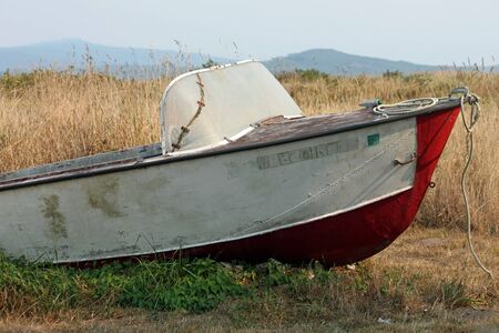 drydock: Old and Weathered Red and White Fishing Boat Abandoned in a Field