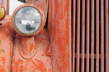 antique fire truck: Weathered Grill of a Red Vintage Fire Truck with One Headlight Stock Photo