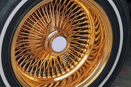 whitewall tire with fancy gold rim stock photo