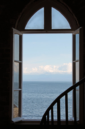 Looking Out an Open  Window to the Blue Ocean and Sky