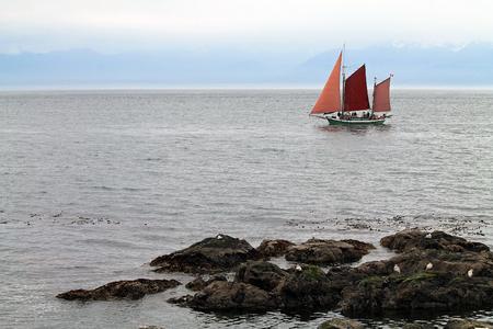 Three-Masted Sailboat Sailing Along a Rocky Shore