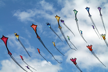 breezy: Colorful Kites Flying in a Cloudy Summer Sky Stock Photo