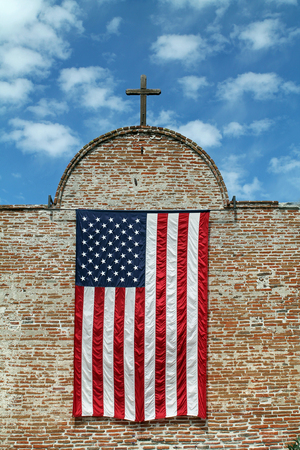 old glory: American Flag and Wooden Cross on a Red Brick Building Stock Photo