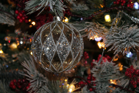 Glittery Silver and Gold Ornament Hanging on a Christmas Tree