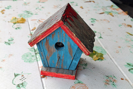 Weathered Wooden Birdhouse with Peeling Red and Blue Paint Stock Photo