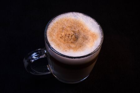 Double Latte with Foam in a Clear Glass Mug against a black background