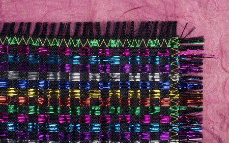 Colorful Woven Placemat with Shiny Metallic Thread on a Black Background