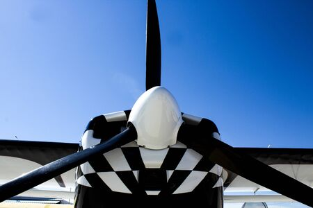 Black Propeller on a Black and White Airplane Agaist a Bright Blue Sky
