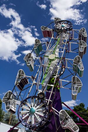 Carnival Ride at the Fair Against a Cloudy Blue Sky