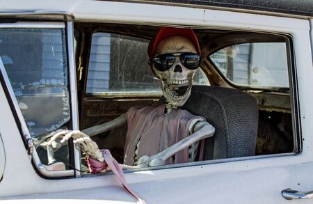 Smiling Skeleton in Sunglasses and a Red Baseball Cap Driving a Car Foto de archivo