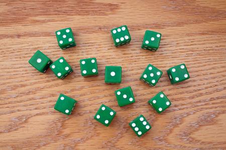 Random Green Dice scattered on an Oak Table