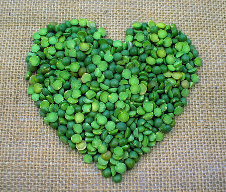 Green Split Peas formed into the shape of a Heart on a Burlap Background
