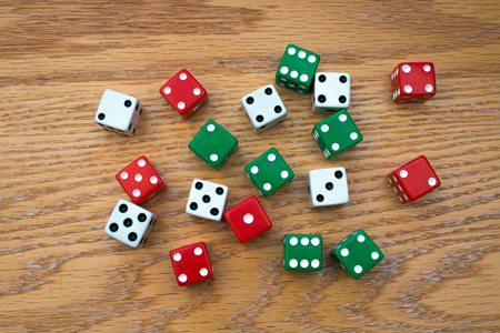 Random Green, Red and White Dice Cubes scattered on an Oak Table Фото со стока