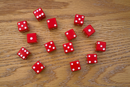 Random Red Dice scattered on an Oak Table