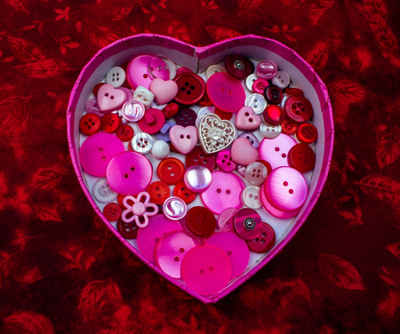Heart Shaped Box Full of Pink, Red and White Buttons on a Red Background