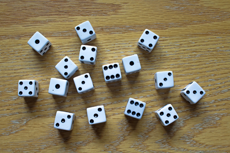 Several Random White Dice scattered on an Oak Table Фото со стока - 94130910
