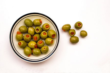 Closeup of a Bowl of Green Stuffed Olives on a white background Stock Photo