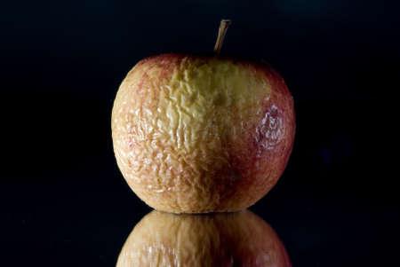 Wizened skin old apple black background  photo