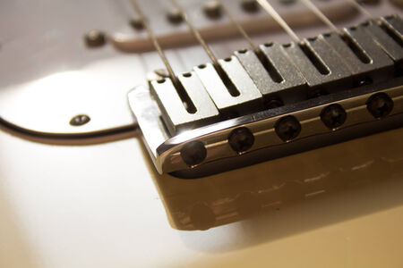 strat: close up of the bridge of a strat, daytime,  white guitar