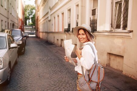 jones: Travel guide. Young female traveler with backpack and with map on the street. Travel concept