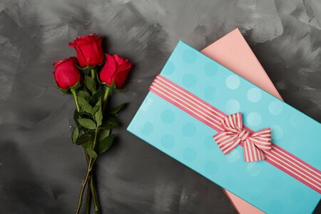 loveheart: Roses with Gift box and pink ribbon on black board, Valentines background, wedding day. Love Concept. Valentines day Card with red hearts on black background with copyspace for greeting text Stock Photo