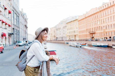 Beautiful girl in a hat smiling at the summer waterfront Imagens