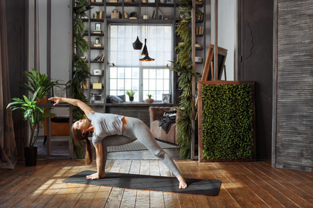 homeware: Young woman in homeware practicing balance yoga pose on carpet in her comfy bedroom.