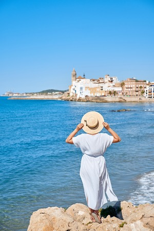 Beautiful girl in a summer dress and hat on the seashore near a background of an old town in Mediterranean Sea, Sitges, Spain. Stock Photo