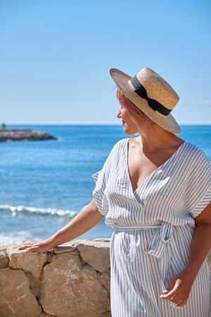 Beautiful girl in a summer dress and hat on the seashore near a background old city europe. Mediterranean Sea, Sitges, Spain Stock Photo
