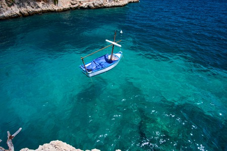 Sea water and granite stones. Boats above coral reef. Spain. Banco de Imagens