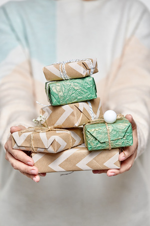 Womans hands hold gift boxes. Christmas or new year decorated gift box