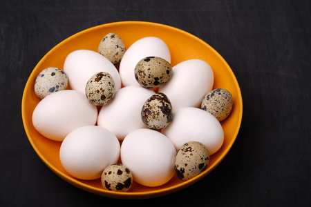 Fresh chicken and quail eggs on yellow plate. Top view. Healthy food and organic farming concept.
