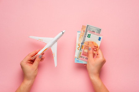 Plane and money in hand on a pink background.  Travel concept Stok Fotoğraf