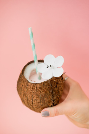 Refreshing summer drinks. Coconut drink on pastel pink background. Trendy summer color Stock Photo