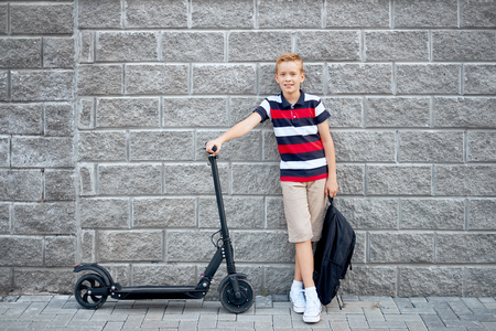 School boy in standing with his electric scooter in the city with backpack. Stock Photo